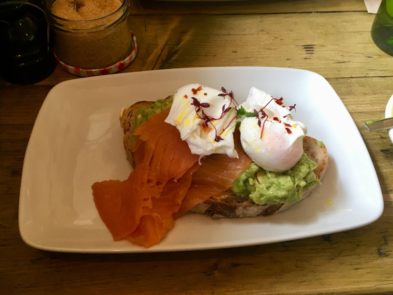 Smashed avocado with poached eggs on toasted sourdough bread from Brickwood Streatham